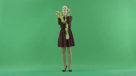 bluntly : A young Christmas woman is looking for a snowfall on the green screen Stock Footage