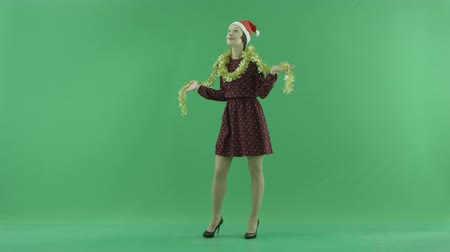 bluntly : A young Christmas woman is circling under the snowfall on the green screen