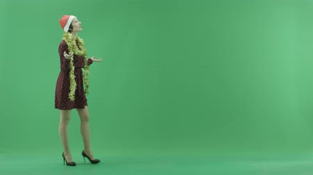 bluntly : A young Christmas woman is going from the left side under the snowfall on the green screen