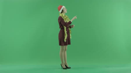 érték : A young Christmas woman is searching for something on a big touch screen on the right hand side on the green screen Stock mozgókép