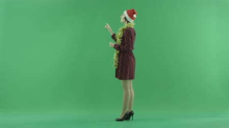 esquerda : A young Christmas woman is searching for something on a big touch screen on the left hand side on the green screen