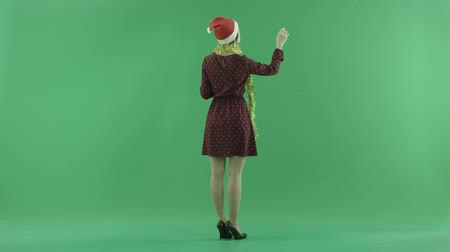 bluntly : A young Christmas woman is searching for something on a big touch screen on the back to the viewer side on the green screen