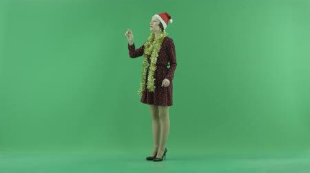 bluntly : A young Christmas woman is searching for something on a big touch screen half-turned on the left hand side on the green screen