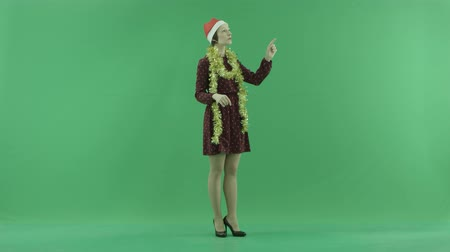 bluntly : A young Christmas woman is searching for something on a big touch screen half-turned on the right hand side on the green screen