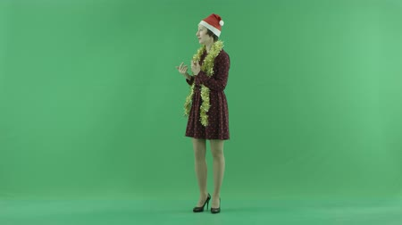 値 : A young Christmas woman calls to someone from the left side on the green screen