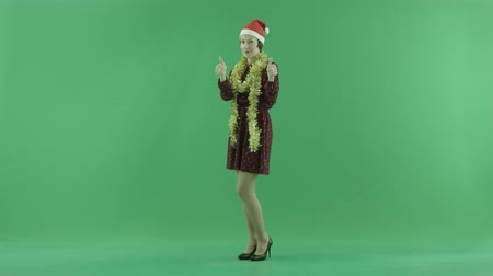érték : A young Christmas woman shows that something is cool on the green screen Stock mozgókép
