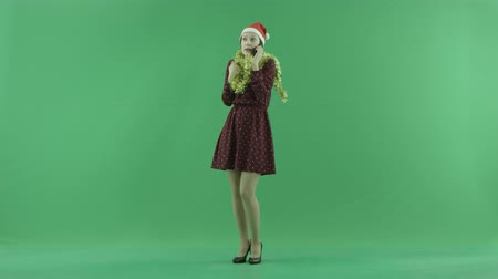 bluntly : A young Christmas woman is calling by phone on the green screen Stock Footage