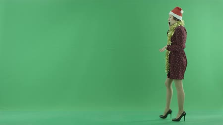 bluntly : A young Christmas woman is going from the right side and talking on her phone on the green screen Stock Footage
