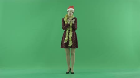 bluntly : A young Christmas woman is writing something with her phone on the green screen