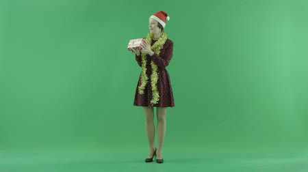 bluntly : A young woman is looking for a Christmas gift and throwing it up on the green screen