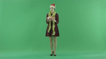 bluntly : A young woman is looking for a Christmas gift and shaking it on the green screen