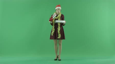 bluntly : A yong woman is opening an empty Christmas gift on the green screen