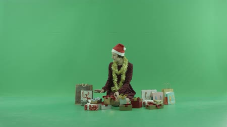 bluntly : A young woman is sitting and looking for a Christmas gifts near her on the green screen