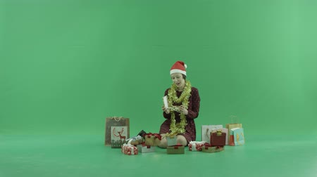 bluntly : A young woman is sitting and opening Christmas gift near herself on the green screen