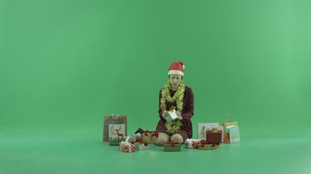 ajándékdobozban : A young woman is sitting and opening empty Christmas gifts around her on the green screen