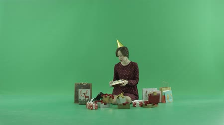 packet : A young woman is sitting and shaking gift boxes around her on the green screen Stock Footage