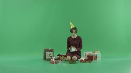 bluntly : A young woman is sitting and opening empty gift boxes around her on the green screen