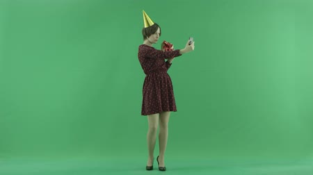 bluntly : A young woman is making selfies with her gift on the green screen Stock Footage