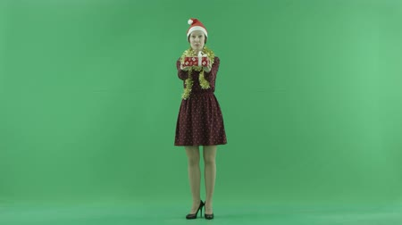 espectador : A young woman is giving a Christmas gift for a viewer on the green screen