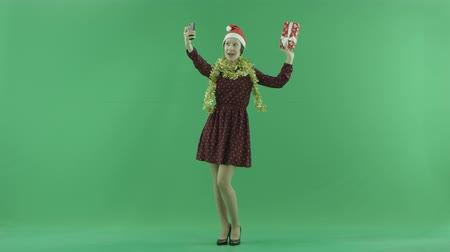 bluntly : A young woman is making selfies with her Christmas gift on the green screen