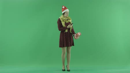 bluntly : A young woman is taking photos of her Christmas gift on the green screen Stock Footage