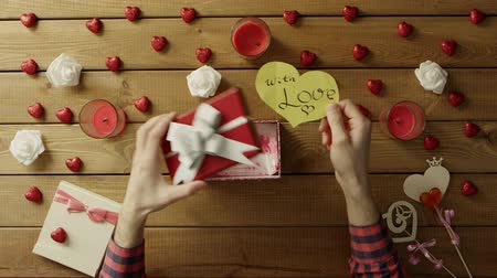 table top shot : Young man puts paper valentine into the present box, top view