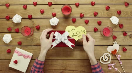 table top shot : Man puts valentine heart onto the gift box, top view