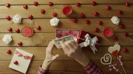 minimalismo : Young man gets money as present in gift box, top view
