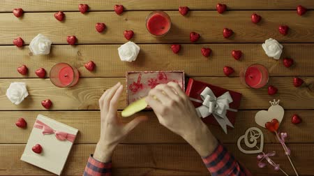 table top shot : Young man gets handmade valentine as valentine day present, top view