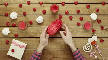 ürpertici : Man looks at plastic human heart by wooden table, top view