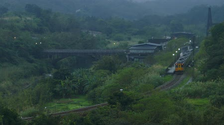 hegyoldalban : Fog weathertrain traveling in a beautiful valley surrounded by green hills and majestic mountains with a bridge spanning across the river in the fog weather
