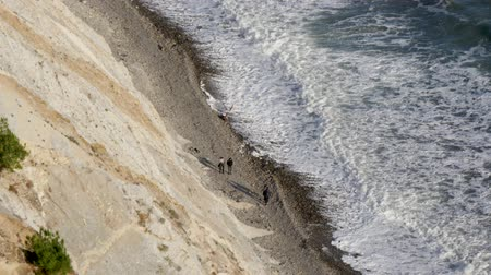ślady stóp : 4 people are walking along the coast, filming from above Wideo