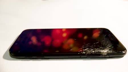 lasca : Smashed glass of mobile phone on table rotating in light with half the screen broken and the frame bent