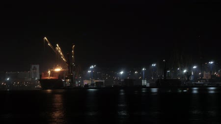 discharging : Container ship discharging at the port at night, port of novorossiysk, unmoored ship go out of the port Stock Footage