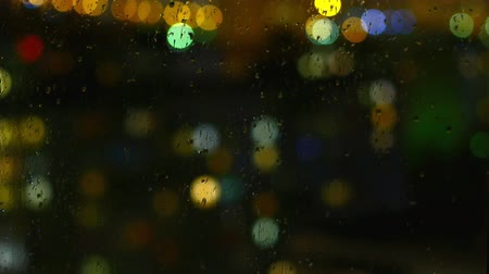 arejado : rainy days, rain drops on window surface and colorful traffic bokeh light