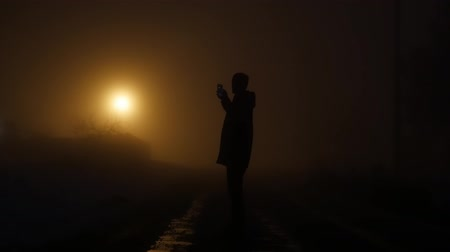 karartmak : low angle view of man looking at smartphone into dark night. mystical fog background. light beams