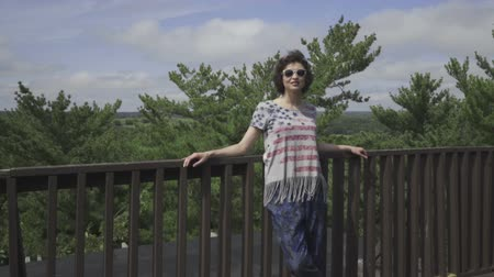 parceiro : woman stands near the railing on forest background Stock Footage
