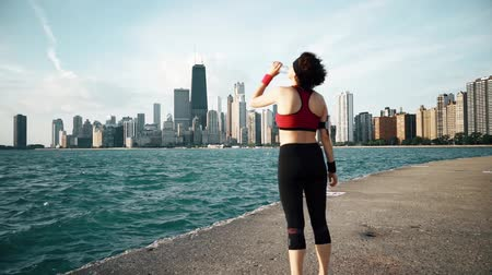 atleta : Runner athlete looking at skyscrapers and drinking water