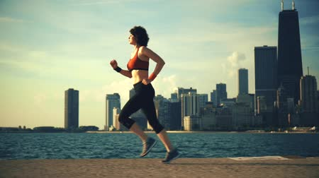 fitnes : Runner athlete running at seaside with skyscrapers on the background Wideo