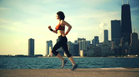 cipő : Runner athlete running at seaside with skyscrapers on the background Stock mozgókép