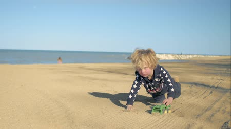 annelik : The boy is playing with a toy green dump truck on the beach.