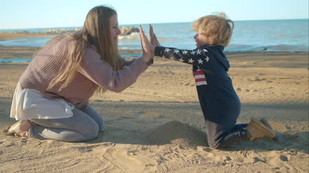 пять : Son gives five to his mother on the beach