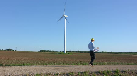 turbine : Engineer goes against the background of windmills