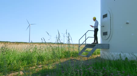 turbine : The engineer is standing on the steps of a windmill. Stock Footage