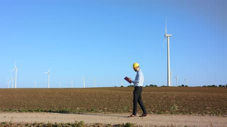 kask : The engineer works with the drawings against the background of windmills Stok Video