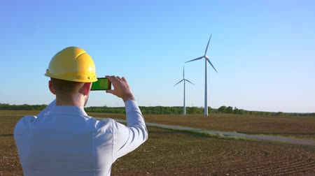 turbine : The engineer stands on the background of windmills and takes pictures