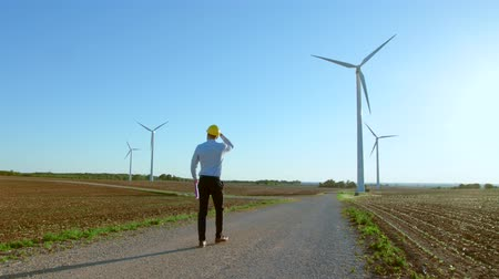 turbine : The engineer goes against the background of the windmills, stops and looks at the windmills. Stock Footage