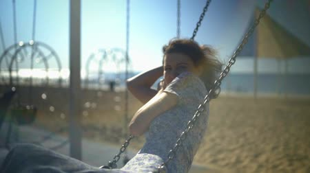 atmosphere : Young beautiful brunette woman is riding on a swing and smiling.
