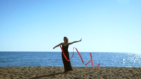 jimnastik : A young woman in a black dress is standing on the sand and doing a drawing of a red ginastic ribbon Stok Video
