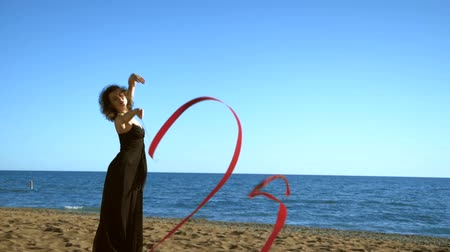 gymnasta : A young woman in a black dress is standing on the sand and doing a drawing of a red ginastic ribbon Dostupné videozáznamy